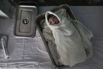 A newborn baby lies in a tray inside the labour room at a government hospital in Kasbathana village in Baran district