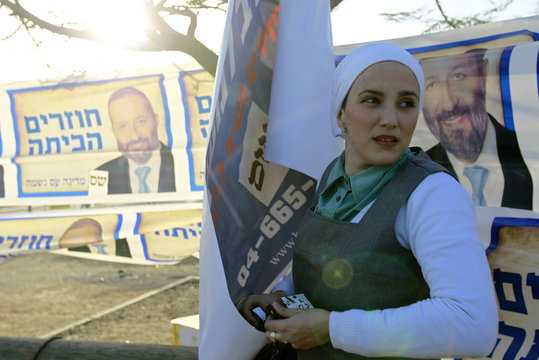 An ultra-Orthodox Jewish woman stands in front of Shas campaign banners in Netivot