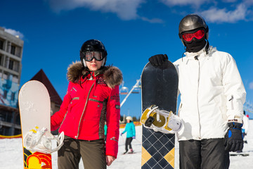 Young stylish couple in ski suits, helmets and ski goggles standing with snowboards in a ski resort