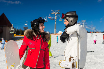 Young smiling couple in ski suits, helmets and ski goggles standing with snowboards in a ski resort