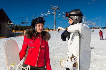 Young man and woman in ski suits, helmets and ski goggles standing with snowboards in a ski-resort