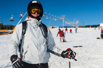 Young man in ski-suit, helmet and ski goggles is skiing in a ski-resort