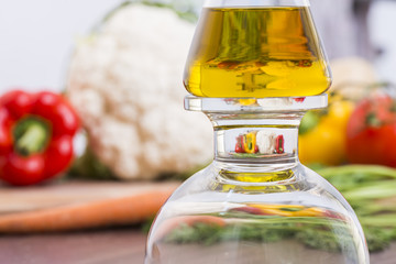 Poster Kitchen Olive oil bottle with magnification of vegetables in the background