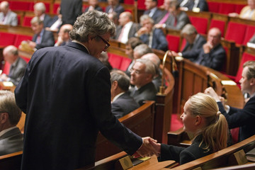 Jean-Louis Borloo, head of the Union Democratic Independant, shakes hands with French National Front party deputy Marion Marechal-Le Pen during the questions to the government session at the National Assembly in Paris