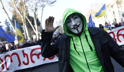 Supporters of the opposition United National Movement march along a street during a protest in Tbilisi