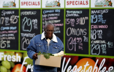 A man carries a box with spinach as he walks past a board displaying food prices outside a grocery shop in Johannesburg