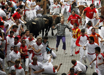 Runners lead Miura fighting bulls to the entrance to the bullring during the fourth running of the bulls of the San Fermin festival in Pamplona