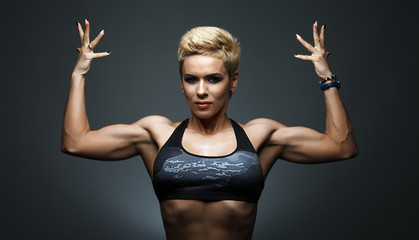 a very fit woman posing her muscular body