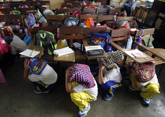 Filipino elementary pupils use protective head gears as they hide under their desks during a simultaneous nationwide earthquake drill in Pasig