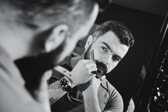 Cute bearded man shearing or shaving his beard. Fashion on the beard