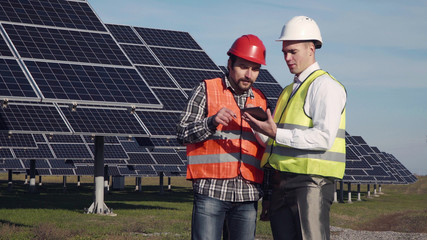Two engineers in uniform and helmets talking at solar power station and using tablet.