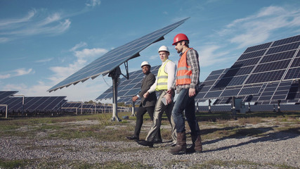 Technician walks with workman and investor through field of solar panels
