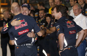 Red Bull Formula One driver Vettel hugs Red Bull technical chief Newey next to team principal Horner after the Japanese F1 Grand Prix at the Suzuka circuit