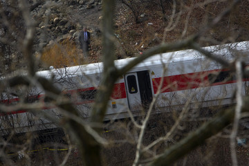 A police officer examines the site of a Metro-North train derailment in the Bronx borough of New York