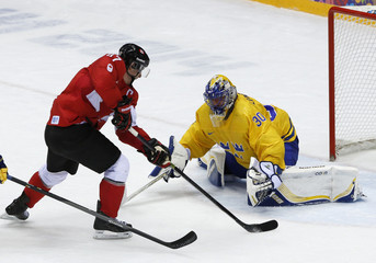 Canada's Crosby drives to the net on Sweden's goalie Lundqvist and then scores during the second period of the men's ice hockey gold medal game at the 2014 Sochi Winter Olympic Games
