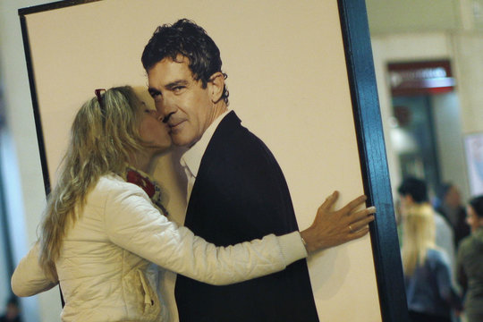 A woman kisses a picture of Spanish actor and director Antonio Banderas while a man takes her picture with a mobile phone during the first day of 17th Malaga Spanish Film Festival in Malaga