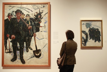"""A visitor looks at the paintings """"Workers in the snow"""", 1910 and """"Sailors in the snow"""", 1910-1912 by Norwegian artist Edvard Munch presented at an exhibition in Frankfurt"""