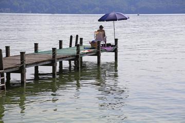 Sommeridylle am Starnberger See: Eine Frau schaut auf den ruhigen See
