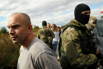 Prisoner of war looks on next to members of self-proclaimed Donetsk People's Republic forces after he was freed by Ukrainian forces in Luhansk region