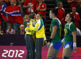 Brazil's goalkeeper Chana Masson is consoled by a team member after their loss to Norway in their women's handball quarterfinals match at the Copper Box venue during the London 2012 Olympic Games