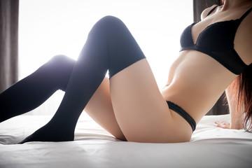 Beautiful slim woman in black panties and knee socks on bed