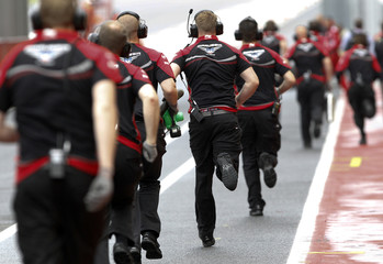 Marussia Formula One staffers run to assist their pilot Pic of France after his car's engine stopped working during an official F1 test session at the Mugello race track