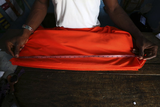 An employee measures cloth to make soccer jerseys at a soccer jersey workshop in the Adjame district of Abidjan