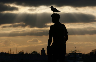 A seagull sits on the 'Mudlarks' sculpture by Michael Peacock during sunset in Portsmouth