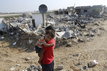 Palestinian boy carries his brother next to the remains of their house, during a 72-hour truce in Khan Younis the southern Gaza Strip