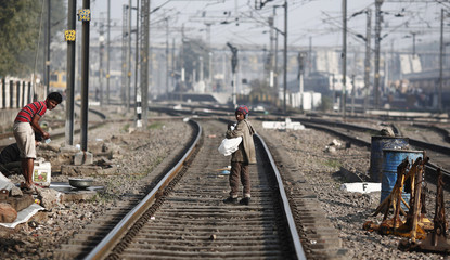 A ragpicker boy walks on the tracks as he searches for plastic bottles for reselling, at a railway station in New Delhi