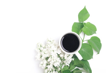 Black coffee in a white mug surrounded by white lilac flower with leafy branch on white background. Flat lay. Top view