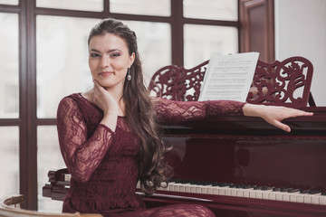 Girl in a red evening dress sits at the piano touch their face and looking at the camera