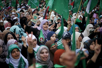 Palestinians take part in a rally marking the 28th anniversary of Hamas' founding, in Gaza City
