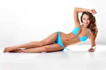 Sexy young brunette woman posing in a bikini.Beautiful perfect figure. Studio portrait. Long slim legs.