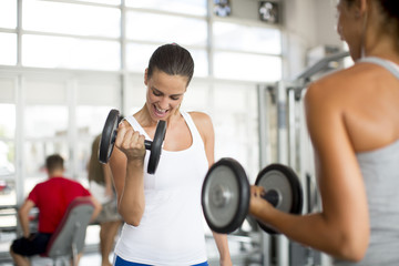 Two young women exercising lifting weights in the gym