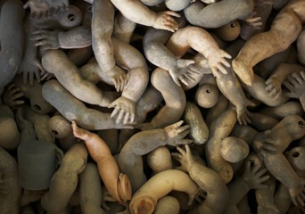 Limbs of dolls are shown as spare parts in a pile ready to be used in customers doll repairs at Sydney's Doll Hospital