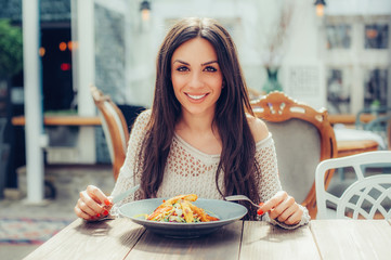Young woman enjoying food in a restaurant, having her lunch break