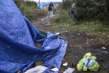 """A stuffed toy is seen in a muddy footpath in the """"New Jungle"""" makeshift camp as unseasonably cool temperatures arrive in Calais"""