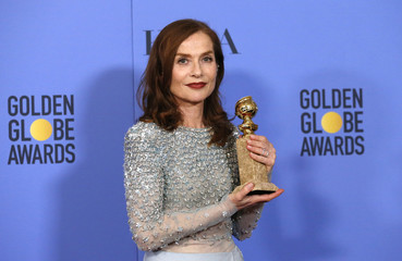 Actress Isabelle Huppert poses backstage with her award at the 74th Annual Golden Globe Awards in Beverly Hills
