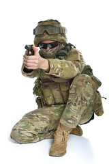 Military man in camouflage uniform, armor vest, dark glasses and helmet with gun aiming at the enemy