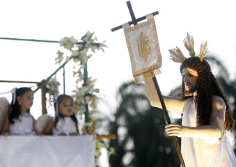 Children dressed as angels look at an image of the Risen Christ during Easter Sunday in Manila