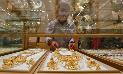 A salesman arranges a gold necklace in a display case inside a jewellery showroom on the occasion of Akshaya Tritiya in Kolkata