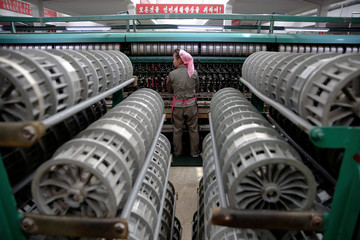 A woman works at the Kim Jong Suk Pyongyang textile mill during a government organised visit for foreign reporters in Pyongyang