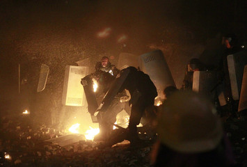 Ukranian riot police take cover behind shields during clashes with Pro-European integration protesters in Kiev