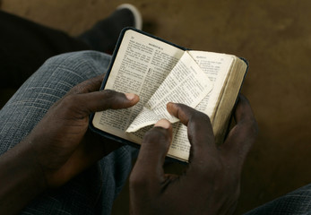 Boy turns a page of a bible during a mass at the Simulambuco church in Cabinda
