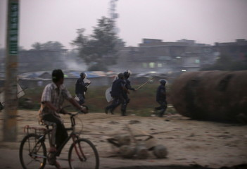 Nepalese police personnel chase Madhesi protesters demonstrating against the new constitution in Birgunj