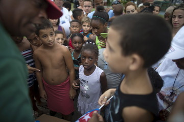 A man distributes Cuban flags to children as they wait for the arrival of Pope Francis from the airport in Havana