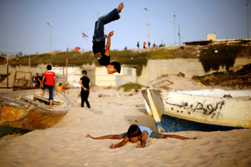 Palestinian boys from Bar Palestine team demonstrate their street workout skills during a training session on a beach in Gaza City