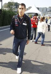 Toro Rosso Formula One driver Sebastien Buemi of Switzerland walks at paddock area at the Suzuka circuit