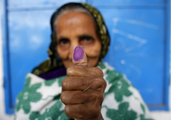 A woman shows her finger that is stained with indelible ink at a polling centre during parliamentary elections in Dhaka